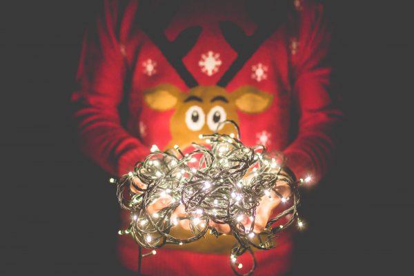 man holding christmas lights